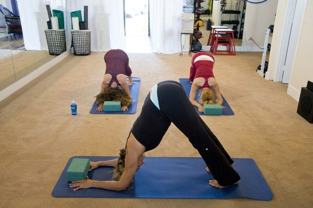 Women in downward facing dog during a yoga class.