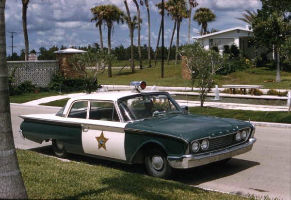 A green and white 1960 Ford Fairlane cop car