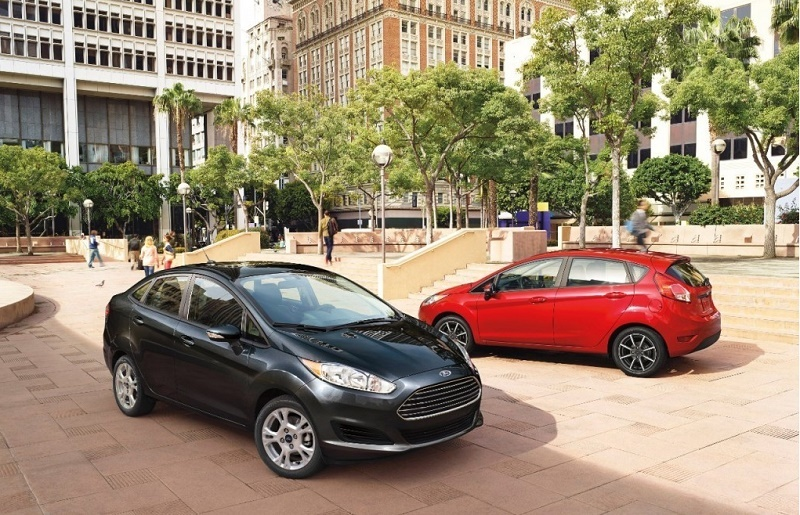 Two 2015 Ford Fiestas in sedan and hatchback form parked next to each other