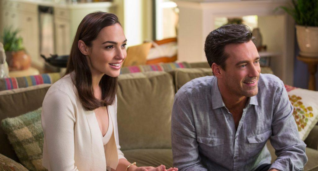 Gal Gadot and Jon Hamm smiling sitting on a couch in Keeping up with the Joneses
