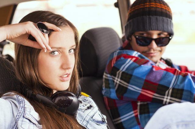 A woman sits next to her partner, who is in the driver's seat.