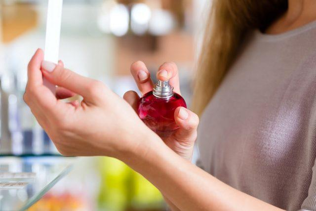 Young woman buying perfume in a shop or store
