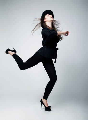 Fashion model girl in black running in studio