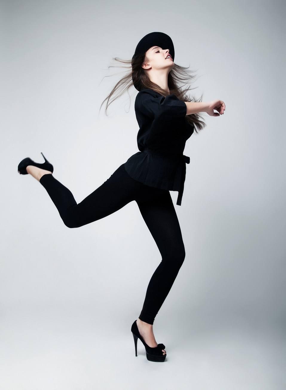 Fashion model girl in black running in studio