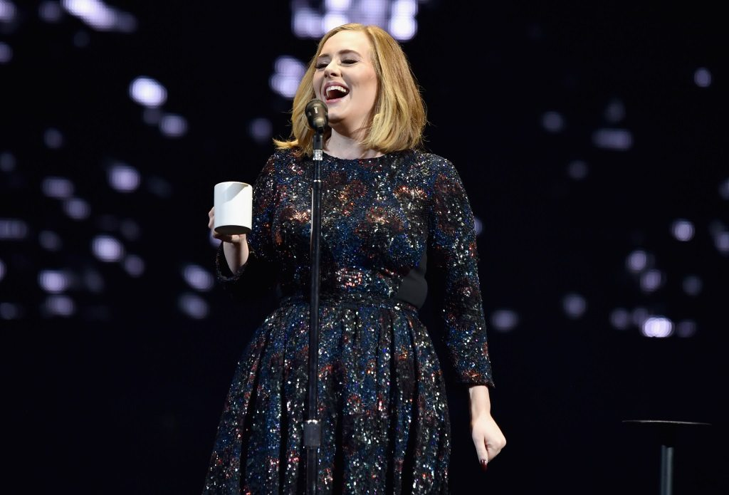 Adele is singing in a black dress on stage.