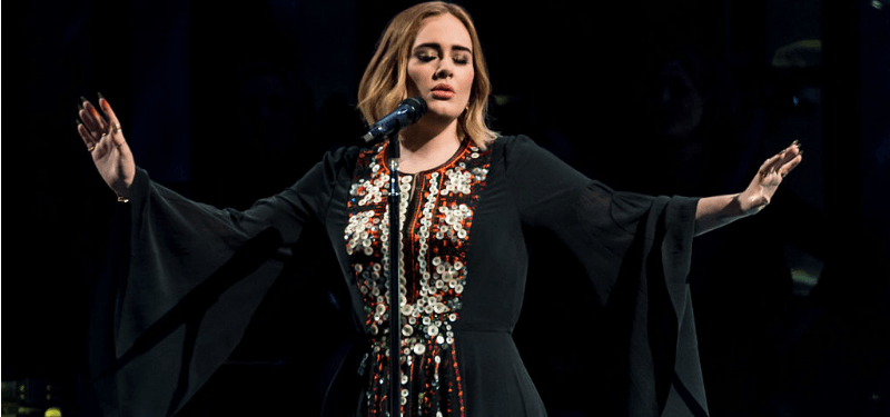 Adele has her eyes closed and her arms stretched out as she's singing on stage.