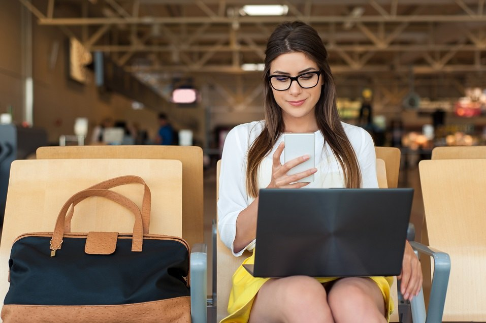 Young female passenger on smart phone and laptop sitting in terminal