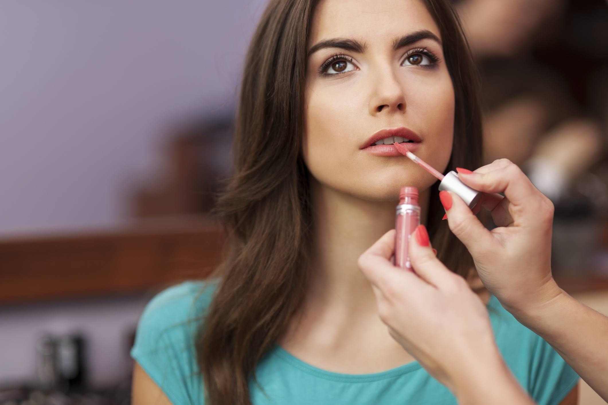 Applying lip-gloss to the lips