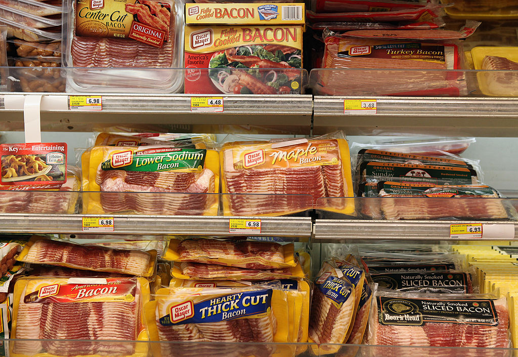 Packages of bacon are displayed on a shelf