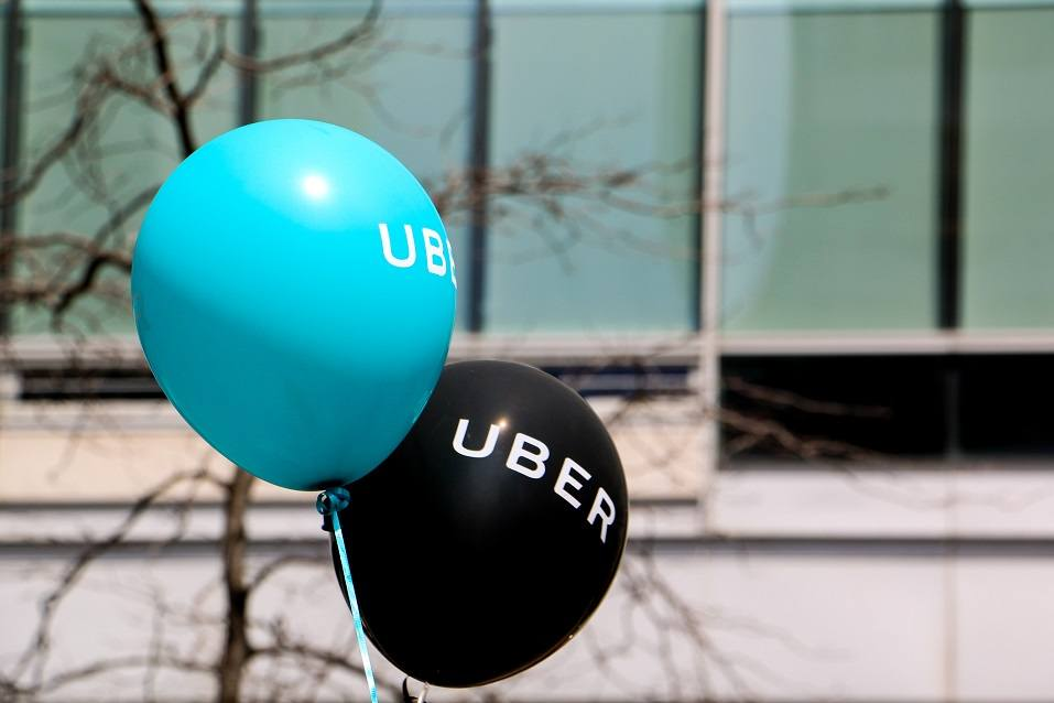 A blue and a black balloon are floating outside at a pro Uber rally