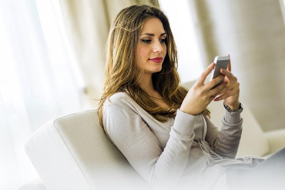 brunette using a phone in a stylish house