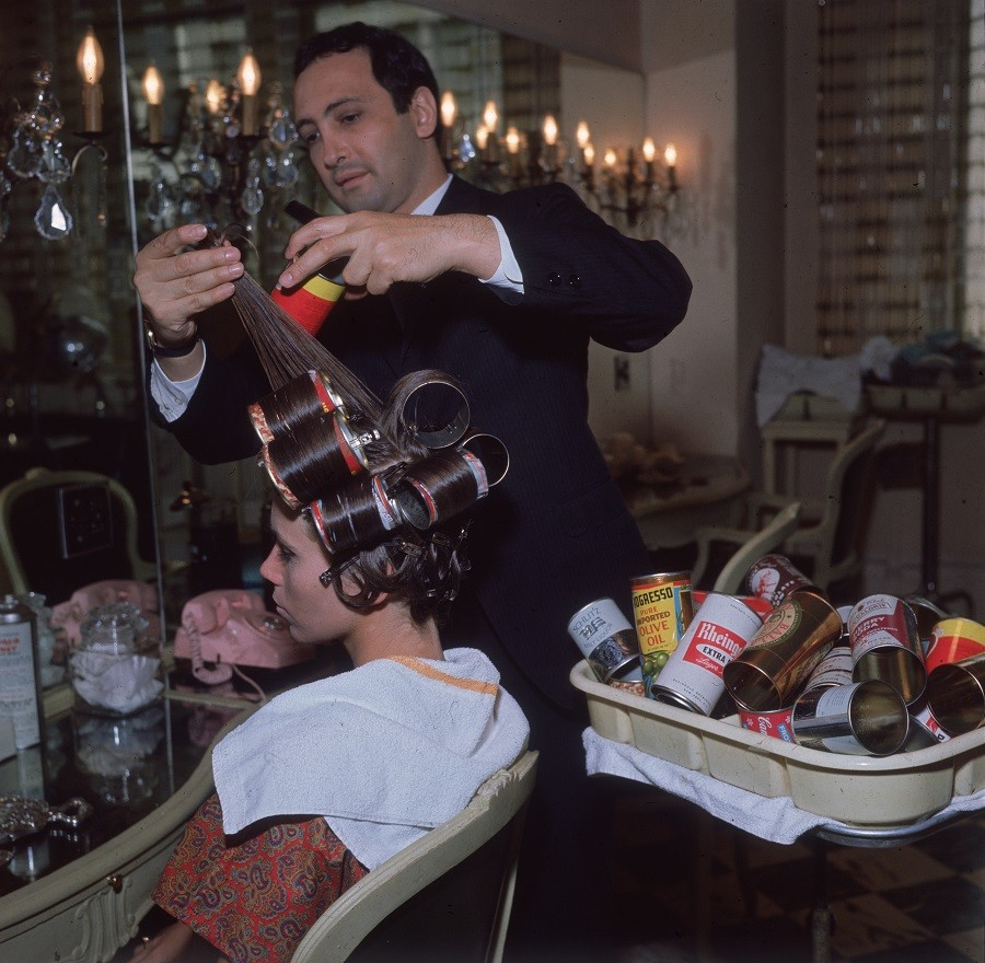A hairdresser styling a woman's hair using beer cans as curlers