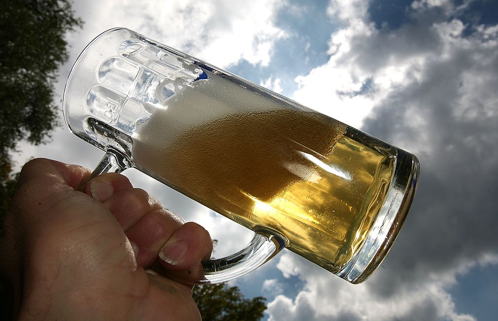 A customer uplifts a mug of freshly draught beer in a beer garden