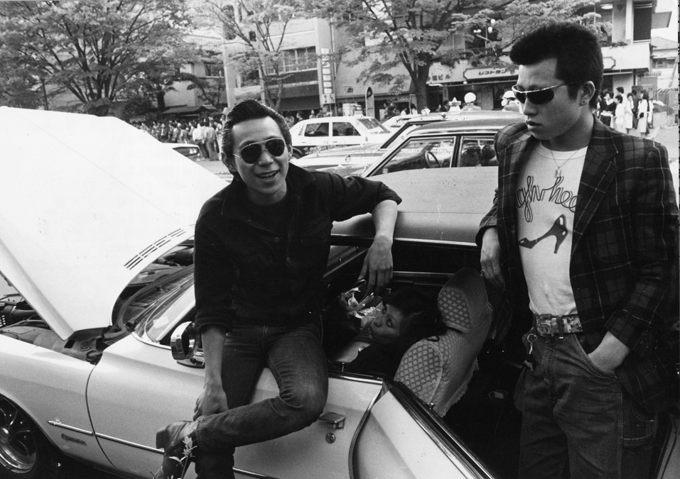 Teenagers hanging out next to a car