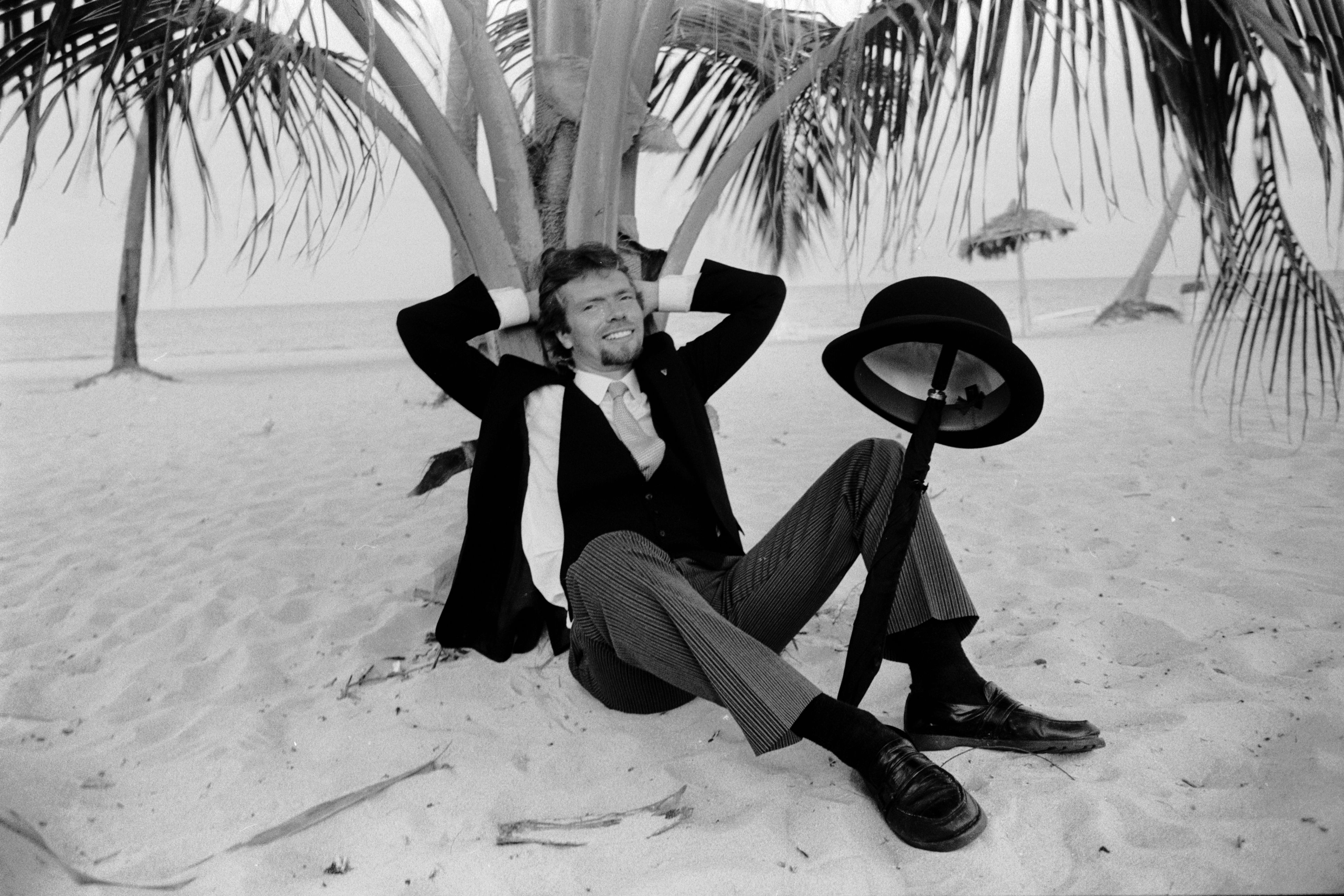 A young billionaire Richard Branson sits under some palm trees, daring you to complete the quiz
