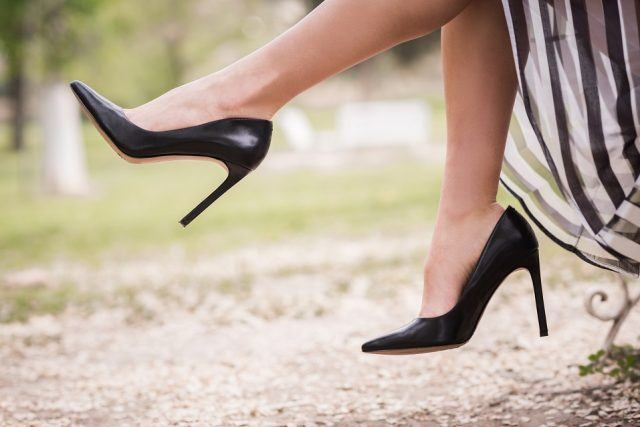 A woman wearing black high heels at a park.