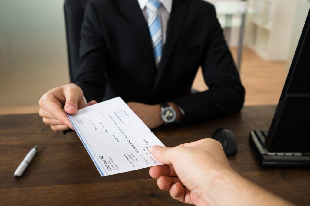 man giving check to employee