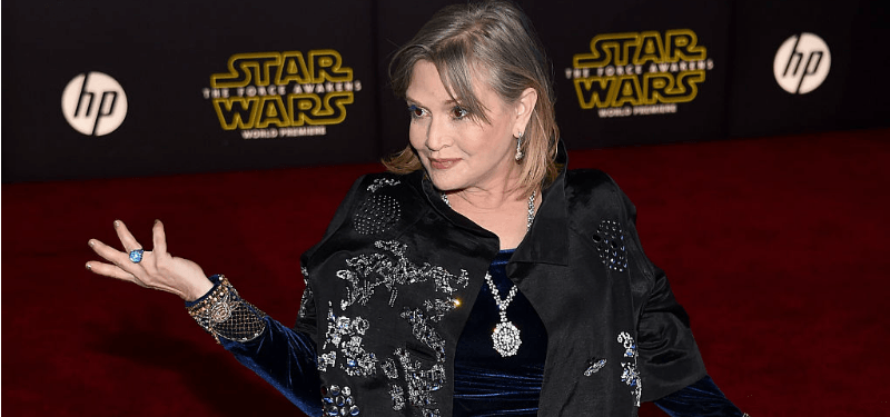 Carrie Fisher has one hand up and is smiling on the Star Wars red carpet.