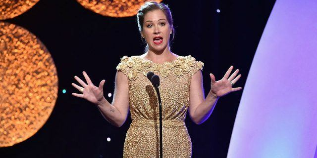 Christina Applegate holding out her hands while speaking on stage.