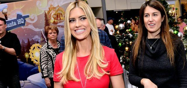 Christina El Moussa in a red dress meeting the press and fans.