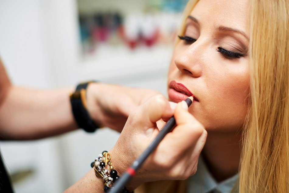 make-up artist contouring lips to model