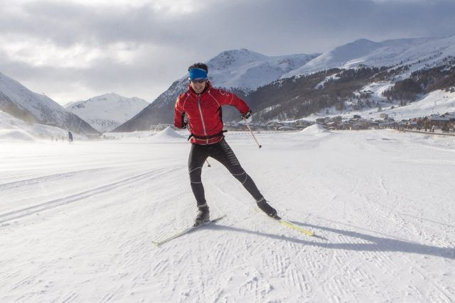 man cross-country skiing in front of winter landscape