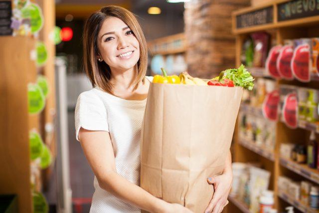 A young woman carrying a shopping bag with groceries