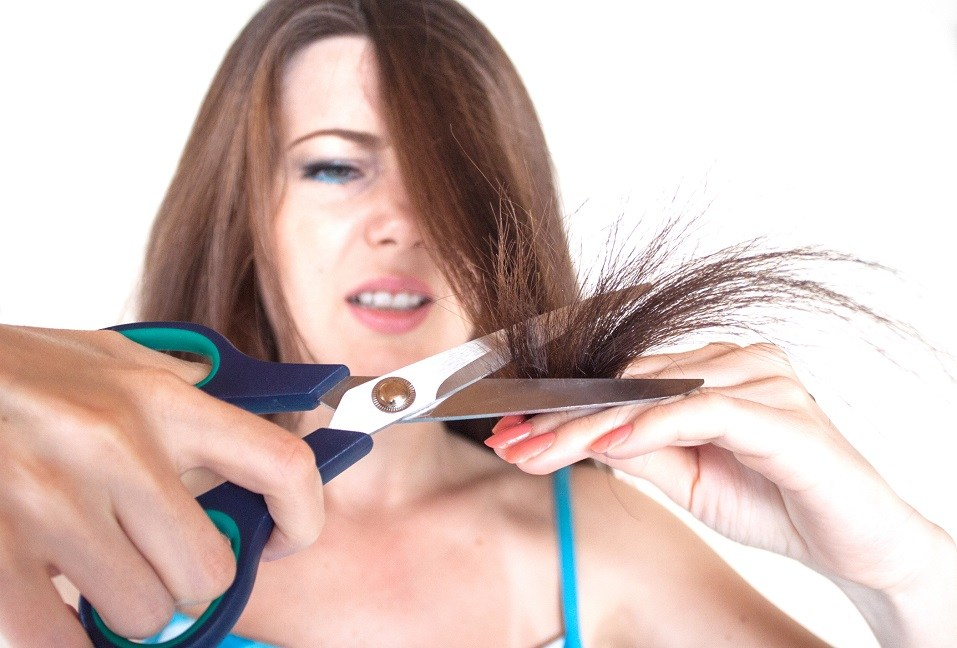 Girl is cutting her damaged hair with scissors