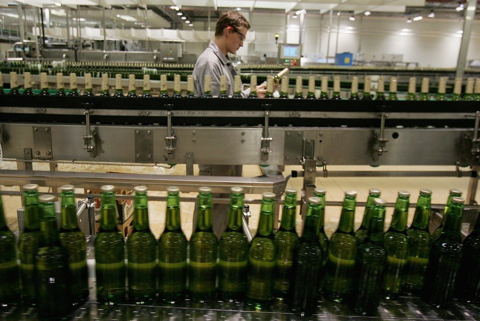 A technician checks a bottle as other bottles of freshly brewed Pilsner-Urquell lager beer run through the bottling plant at the Prazdroj brewery