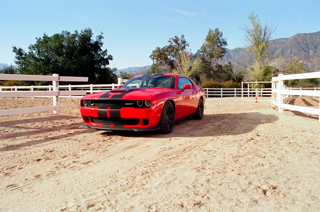 A red 2016 Dodge Challenger Hellcat sits parked on a sandy track