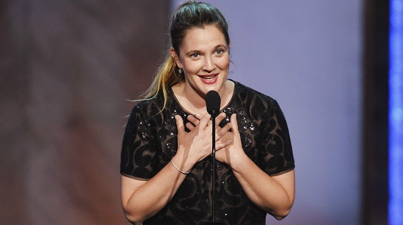 Drew Barrymore onstage in a black dress speaking into a microphone