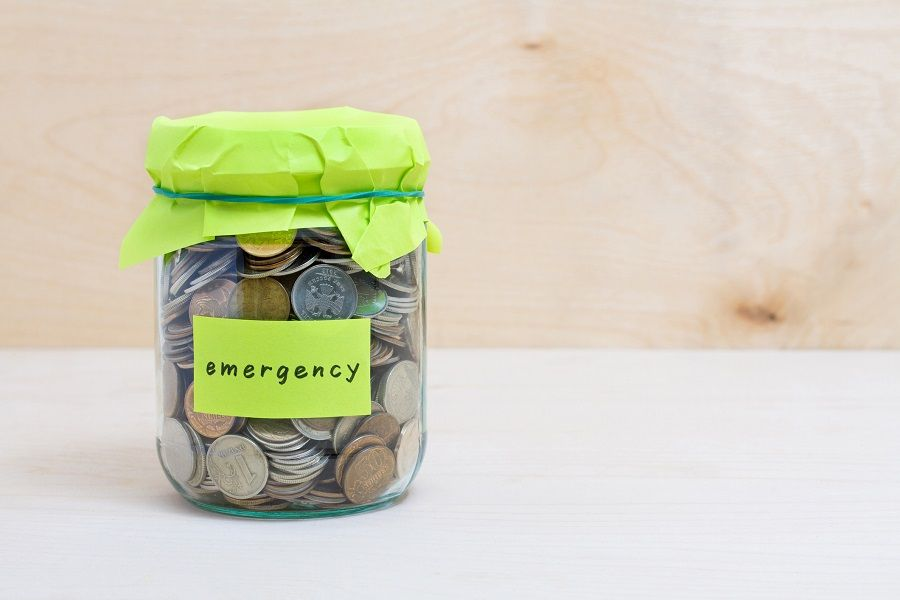 Coins in glass money jar with emergency label
