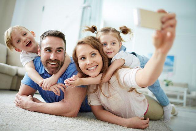 young family takes a selfie on the floor