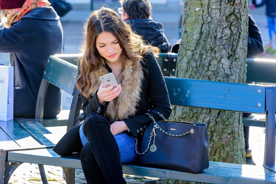 woman outside sitting on bench while on her phone