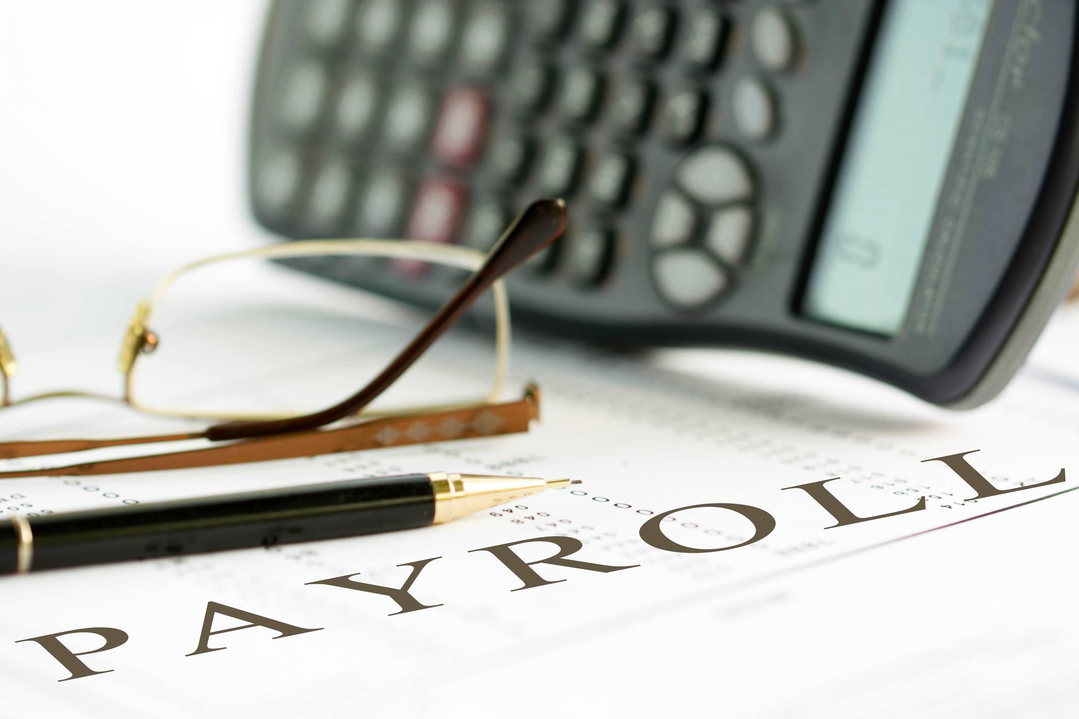 payroll sheet wtih pen and glasses