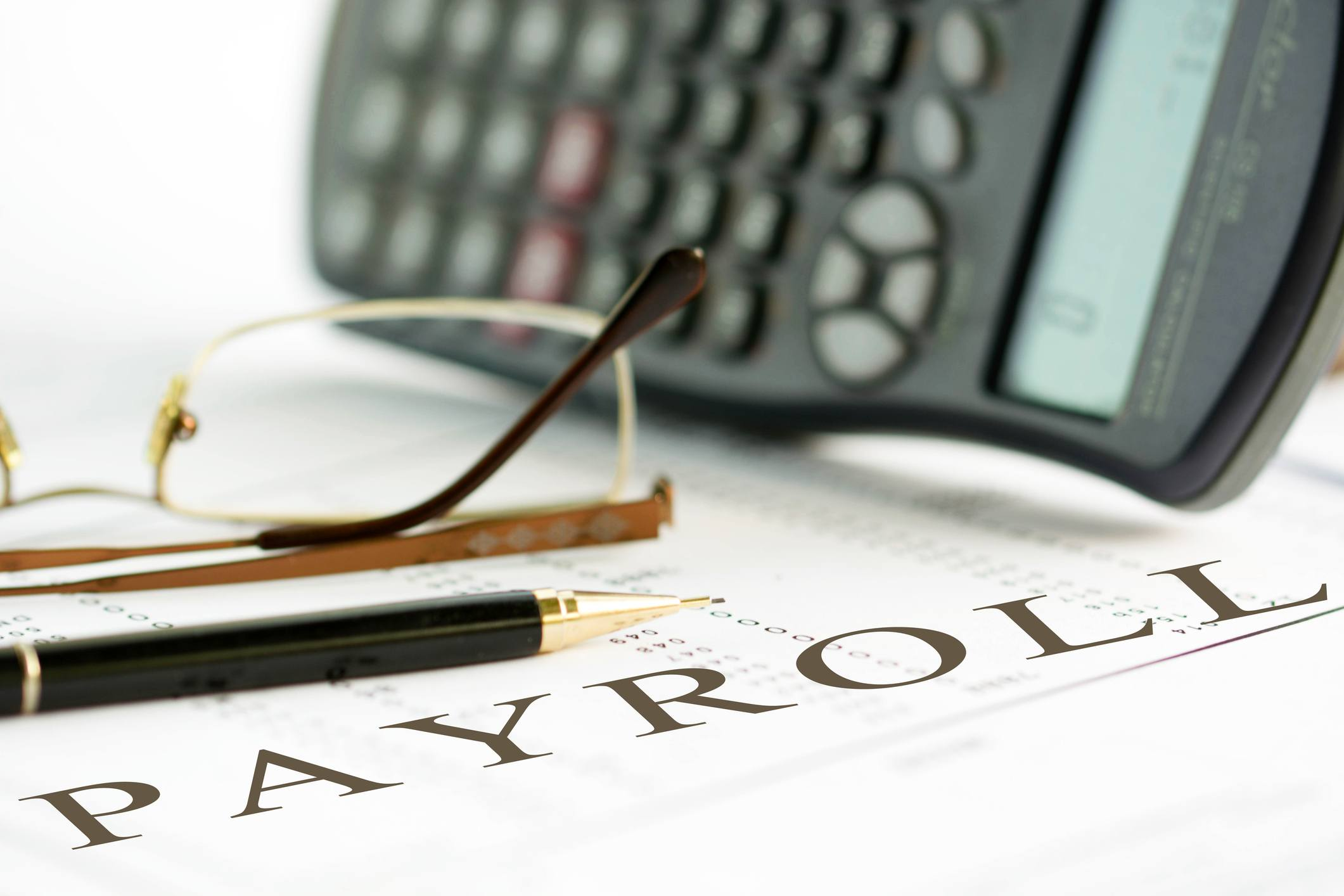 Pen, glasses, and a calculator sitting on top of payroll documents