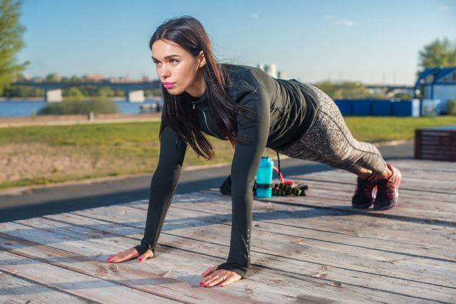 Fit woman doing full plank core exercise.