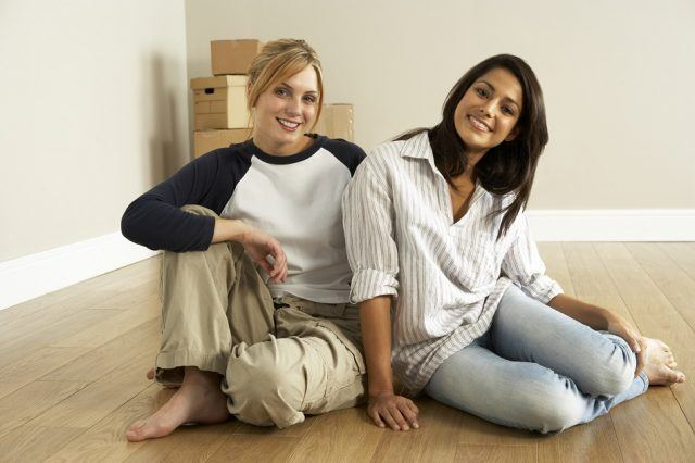 friends sitting on the floor of empty new home