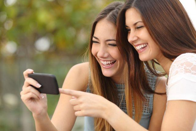 Two women friends laughing and looking at the Bitmoji app