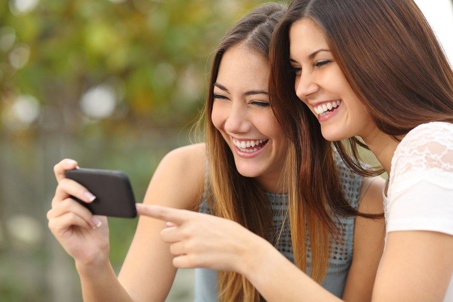 Two women friends laughing and sharing social media videos