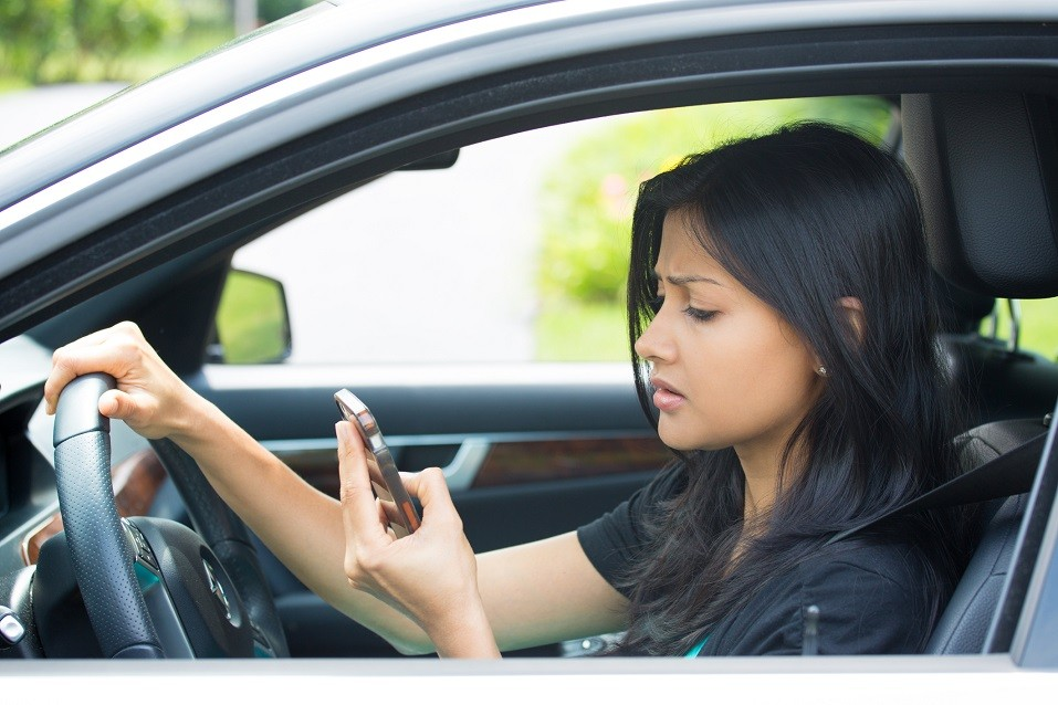 young woman driving in black car and checking her phone