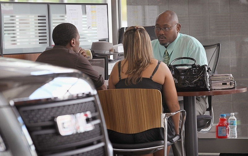 LINCOLNWOOD, IL - AUGUST 30: Wil Jordan (R), a salesman at the Grossinger Autoplex car dealership, speaks with customers on August 30, 2010 in Lincolnwood, Illinois. A strong demand for automobiles helped to drive consumer spending in July to its strongest pace in four months.