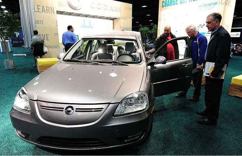 Potential car buyers view the CODA electric car February 2, 2012 at the 2012 Washington Auto Show at the Walter E. Washington Convention Center in Washington, DC. The CODA sedan, is a four-door, five passenger electric car powered by a battery pack that is expected to deliver a range of 150 miles (240 km) per charge according to CODA. The auto show runs through February 5.