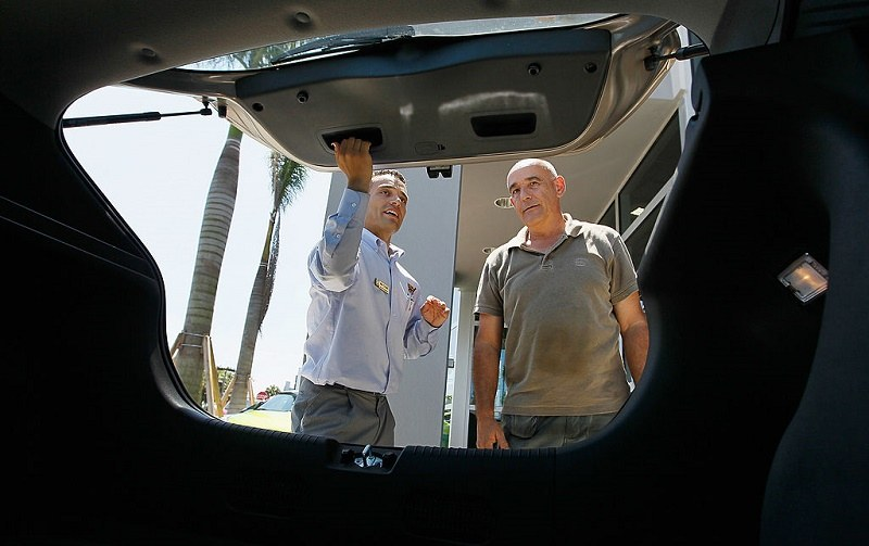 A salesman assists a customer in inspecting a car on the lot