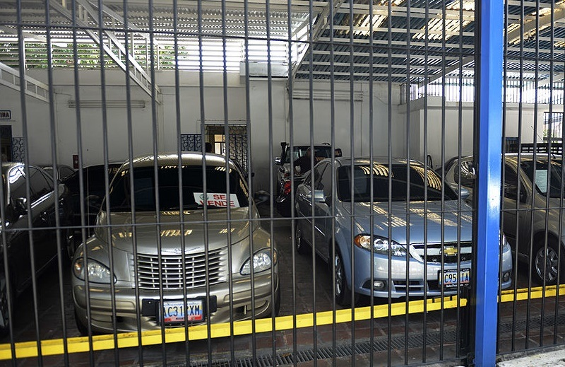 A man looks at used cars at a car dealer in Caracas on October 30, 2012. Venezuela, the country with the largest oil reserves and the world's cheapest gasoline, has the peculiarity that the supply of new cars has dropped and prices soared, especially that of the used ones.
