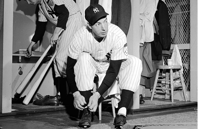 American baseball player Joe DiMaggio (1914 - 1999) in the changing room of the Yankee Stadium as the batboy removes his bats from the locker.