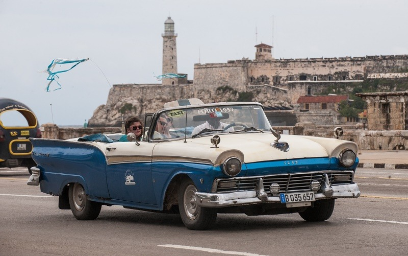 Tourists travel in a taxi, on January 8, 2014 in Havana. Taxi drivers in Cuba, who until now have been government employees, are to become self-employed workers, the latest in a raft of economic reforms on the Communist island. State-run media reported on Wednesday that the government was making the change with the goal of improving the island's slow and unreliable livery service. It also hopes to pare down the bloated government payroll on this island of some 11.1 million people.