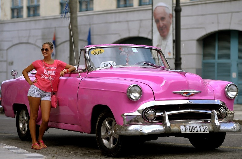 A tourist leans by a taxi in front of a portrait of Pope Francis marking his visit to Cuba, in a street of Havana on September 17, 2015. The pope is visiting Cuba from September 19 to 22, the first stop on a trip that also will take him to the United States. In Cuba, he will visit Havana, the northeastern city of Holguin and Santiago de Cuba on the southeastern end of the island.