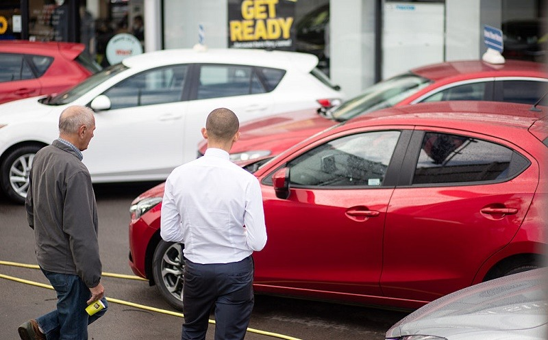 A customer looks at a brand new Mazda car offered for sale at a dealership