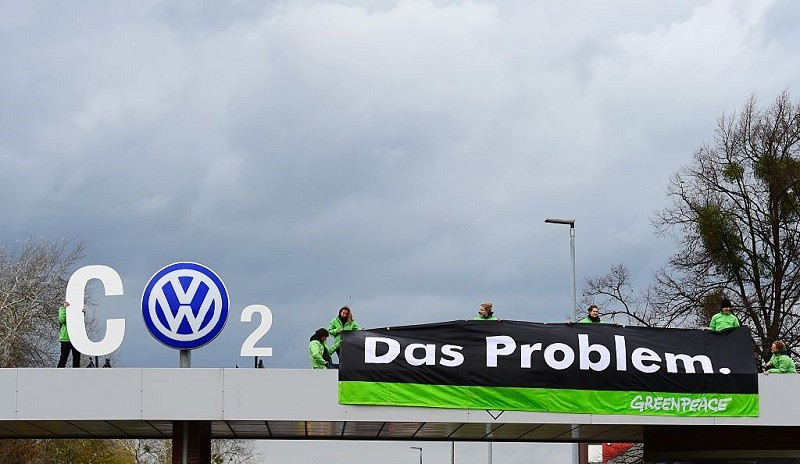 """Greenpeace activists demonstrate at the entrance to the Volkswagen (VW) plant in Wolfsburg, central Germany, on November 9, 2015. Germany's consumers association wants auto giant Volkswagen to offer vouchers as a form of compensation to German customers affected by the massive pollution cheating scandal. VW is engulfed in a massive pollution scandal that has so far centred on so-called defeat devices, sophisticated software fitted into diesel engines to skew the results of tests for nitrogen oxide emissions. But the embattled auto giant said an internal probe had uncovered """"inconsistencies"""" on carbon emissions as well, affecting not only diesel engines but petrol engines, too. AFP PHOTO / JOHN MACDOUGALL"""